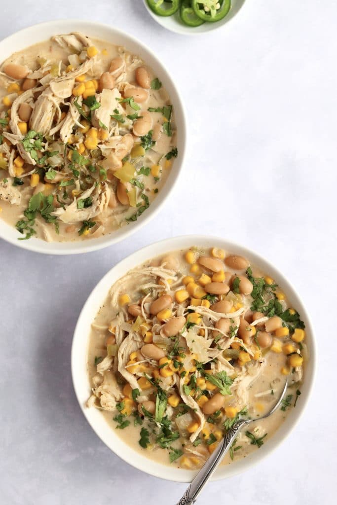 Two bowls of creamy white chicken chili with corn and white beans