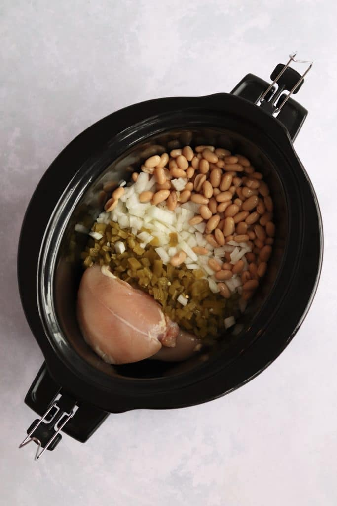 Chicken chili ingredients - chicken breasts, green chiles, onion, and white beans - in a crock pot