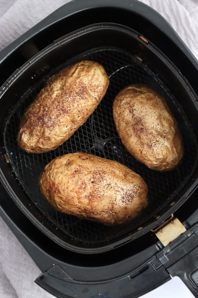 Three baked potatoes in an air fryer