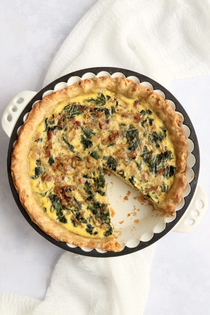 Baked spinach pancetta quiche with a slice taken out