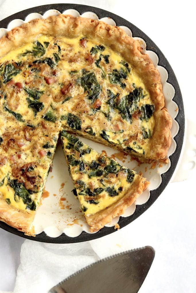 Baked onion pancetta spinach quiche with a slice cut