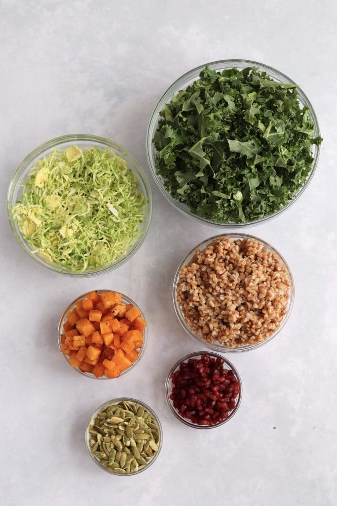 Shedded Kale, Sliced Brussels sprouts, farro, roasted butternut squash, pomegranate, and pumpkin seeds in glass prep bowls