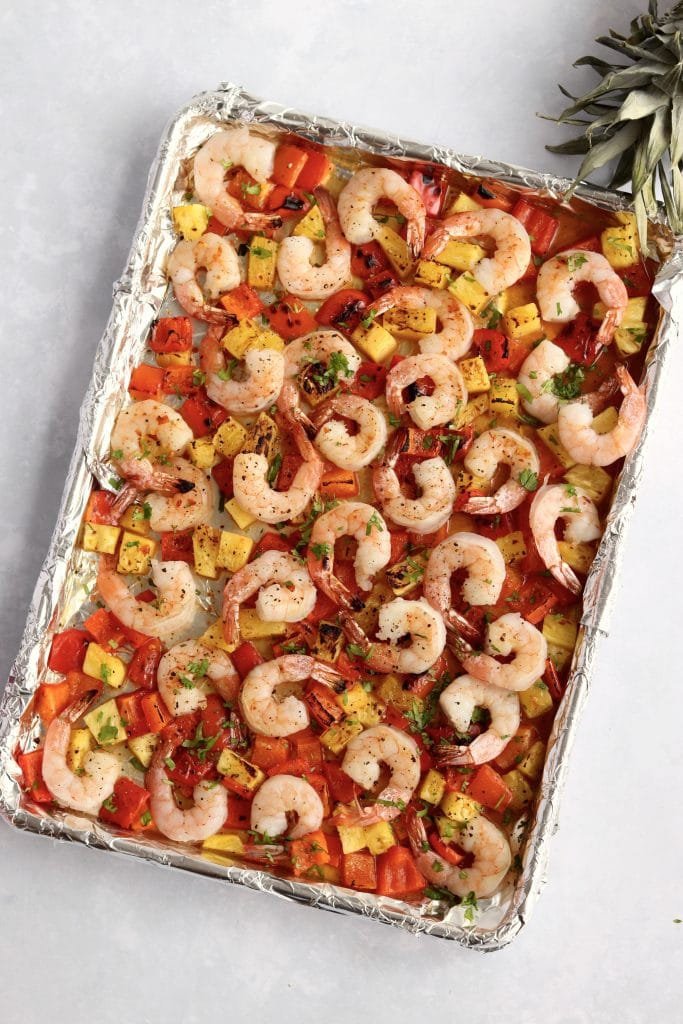 Pineapple, shrimp, and bell peppers roasted on a sheet pan.