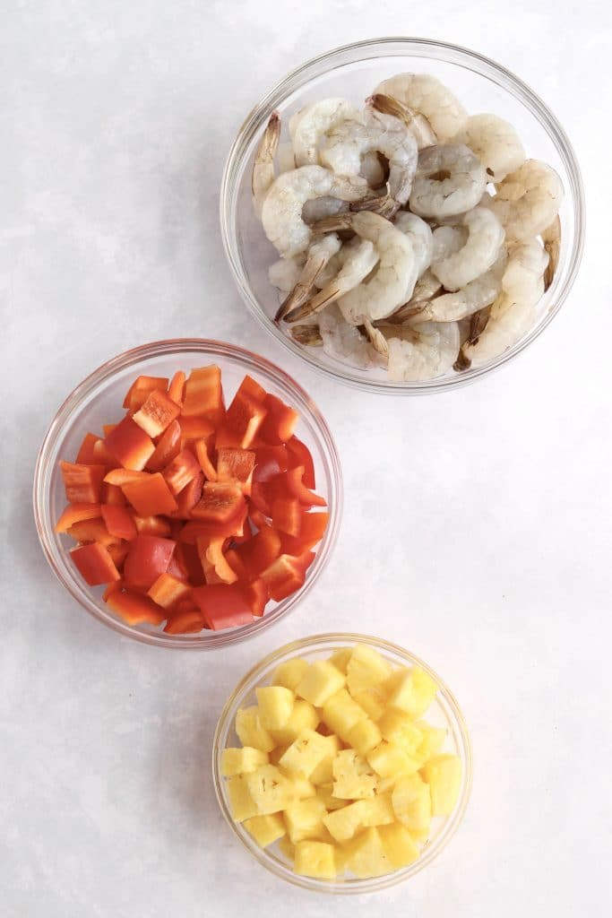 Raw shrimp, red bell pepper, and pineapple in prep bowls.