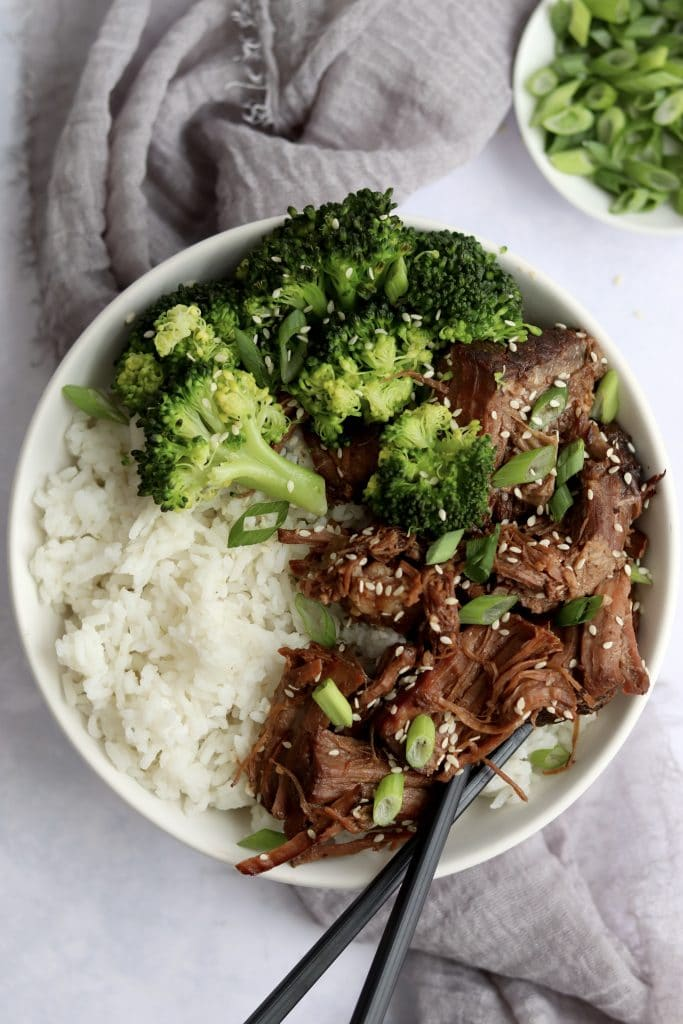 Shredded slow cooker Korean beef in a bowl with rice and broccoli