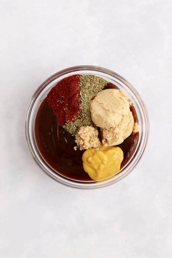 barbecue sauce, mustard, brown sugar, garlic, and spices in a glass bowl