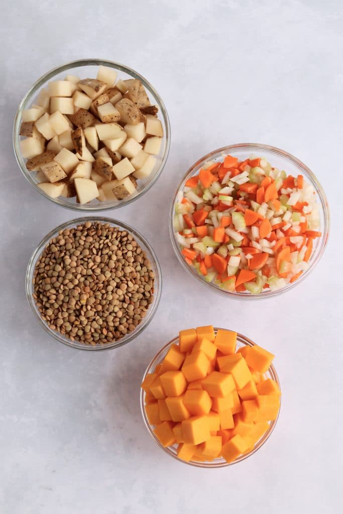 Diced potatoes, mirepoix, lentils, and butternut squash in glass prep bowls