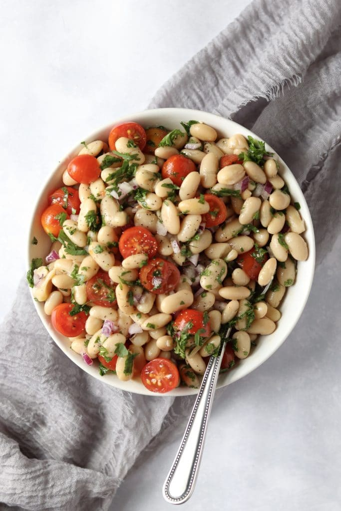 Bowl of white bean salad with tomatoes and fresh herbs