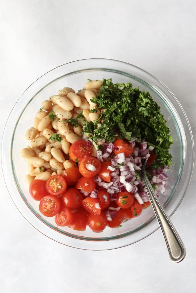 White beans, tomatoes, red onion, and herbs in bowl