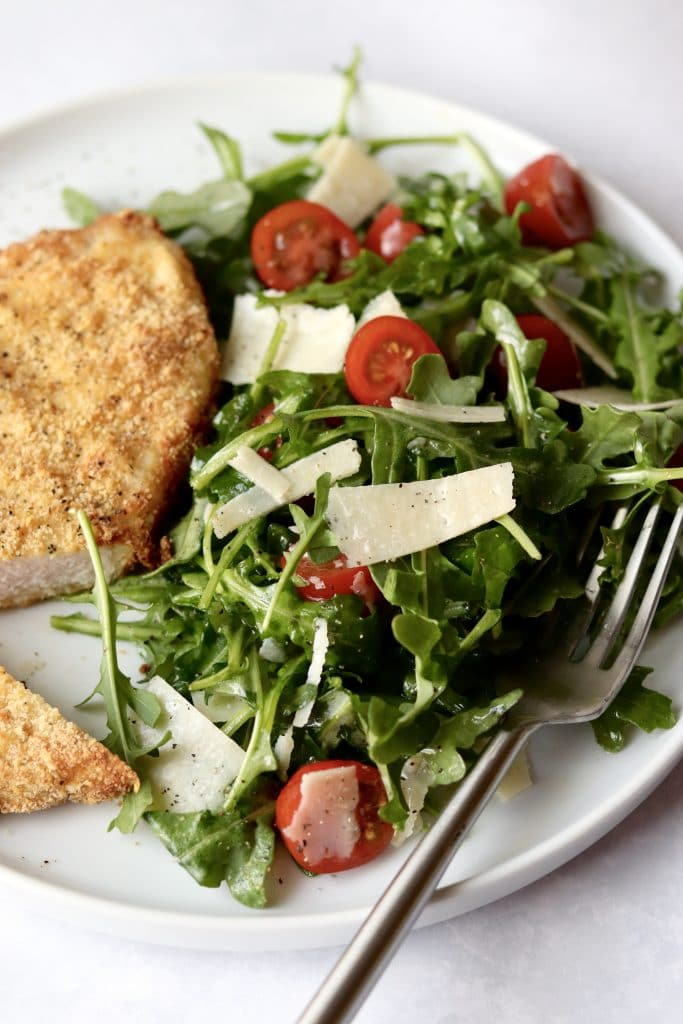 arugula salad with pork milanese on a plate