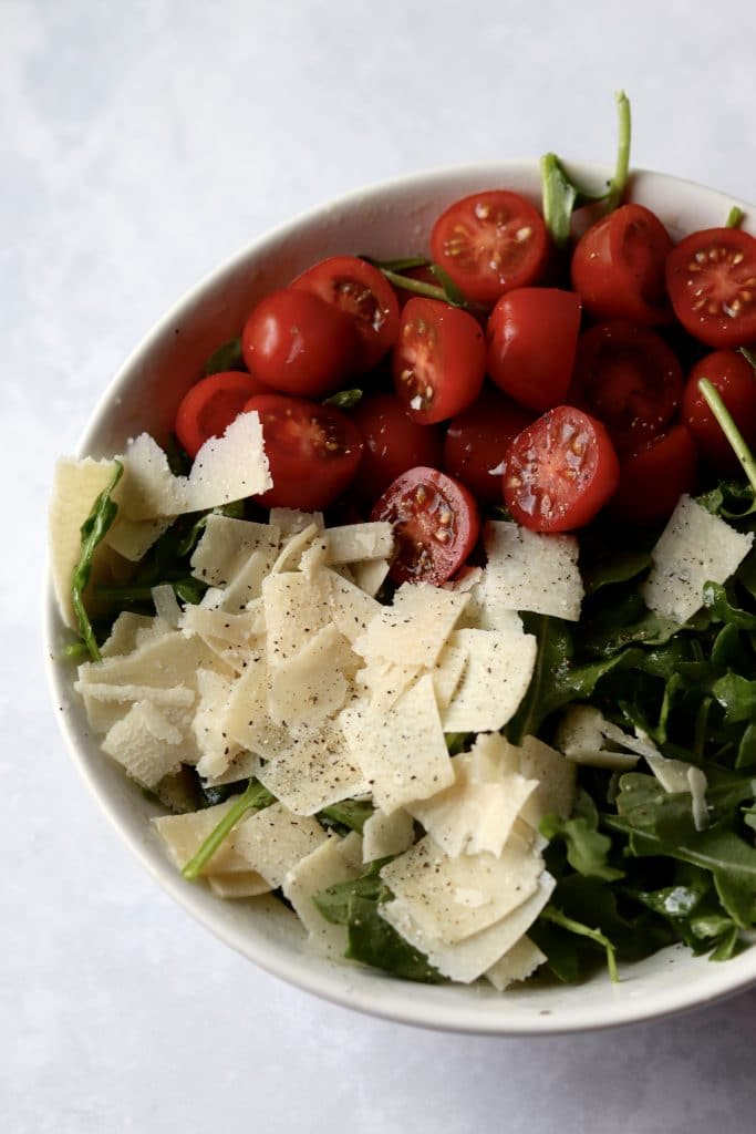 arugula, tomatoes, and shaved Parmesan in bowl for salad