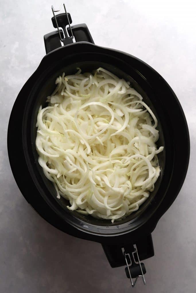 Raw, sliced onions in a crockpot