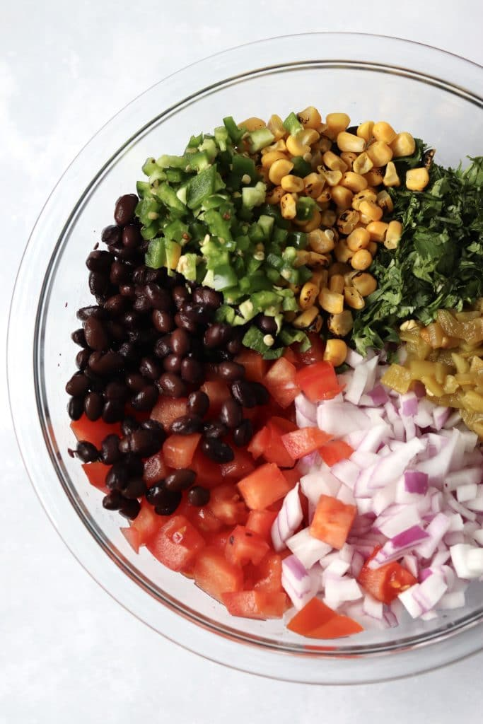 Black beans, tomatoes, red onion, jalapeño, corn kernels, and cilantro in bowl
