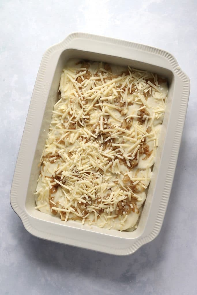 cheese sauce and caramelized onions over potatoes