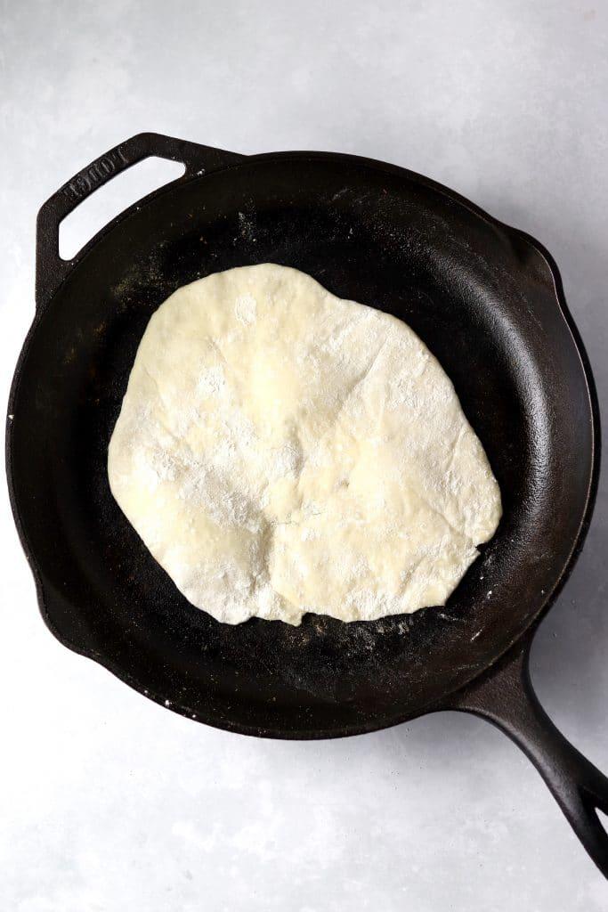 flatbread dough in hot skillet