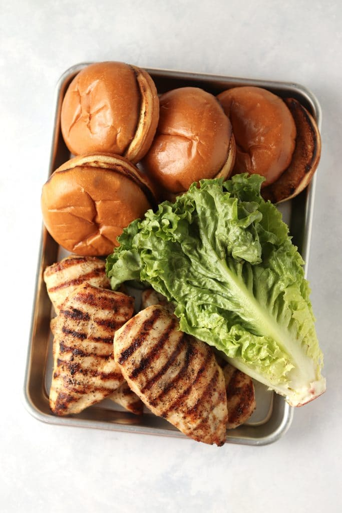 grilled chicken breasts, romaine lettuce, and buns on a sheet pan