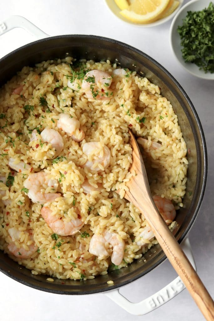 Lemon butter shrimp with orzo and a wooden spoon in a pot