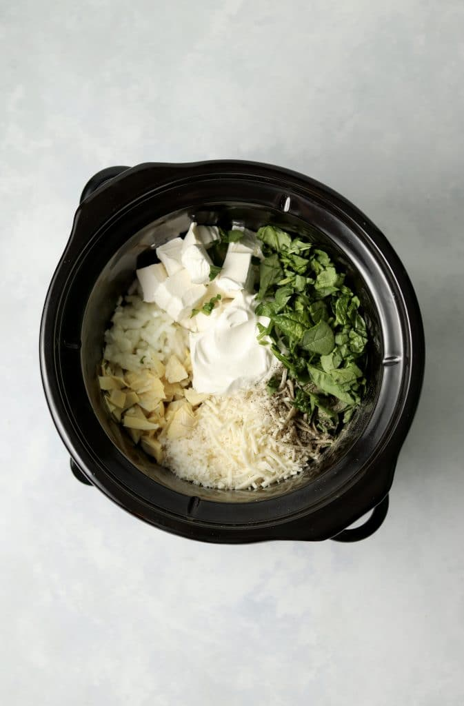 spinach, cream cheese, sour cream, artichokes, and shredded cheese in a crockpot