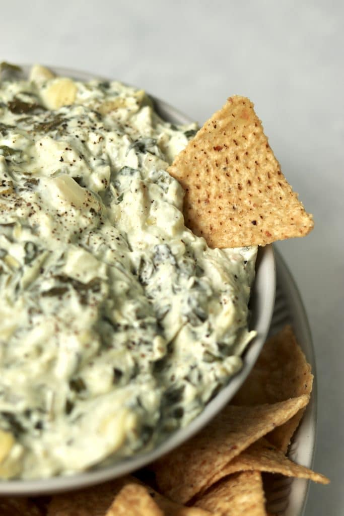 Tortilla chip being dipped into spinach artichoke dip