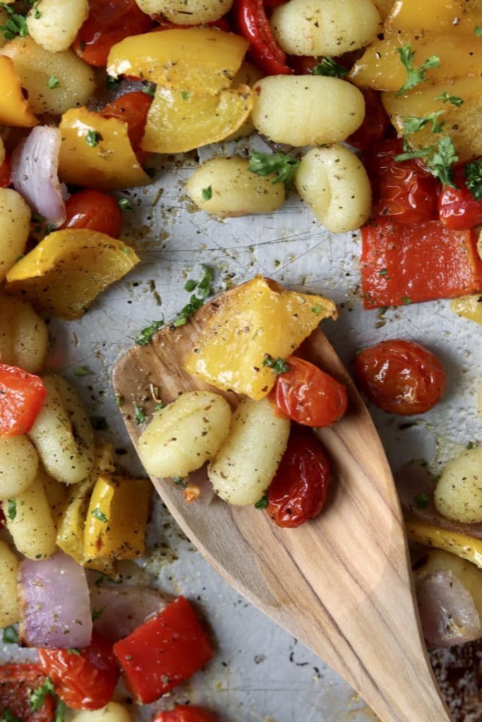 vegan sheet pan gnocchi and veggies with a wooden spoon