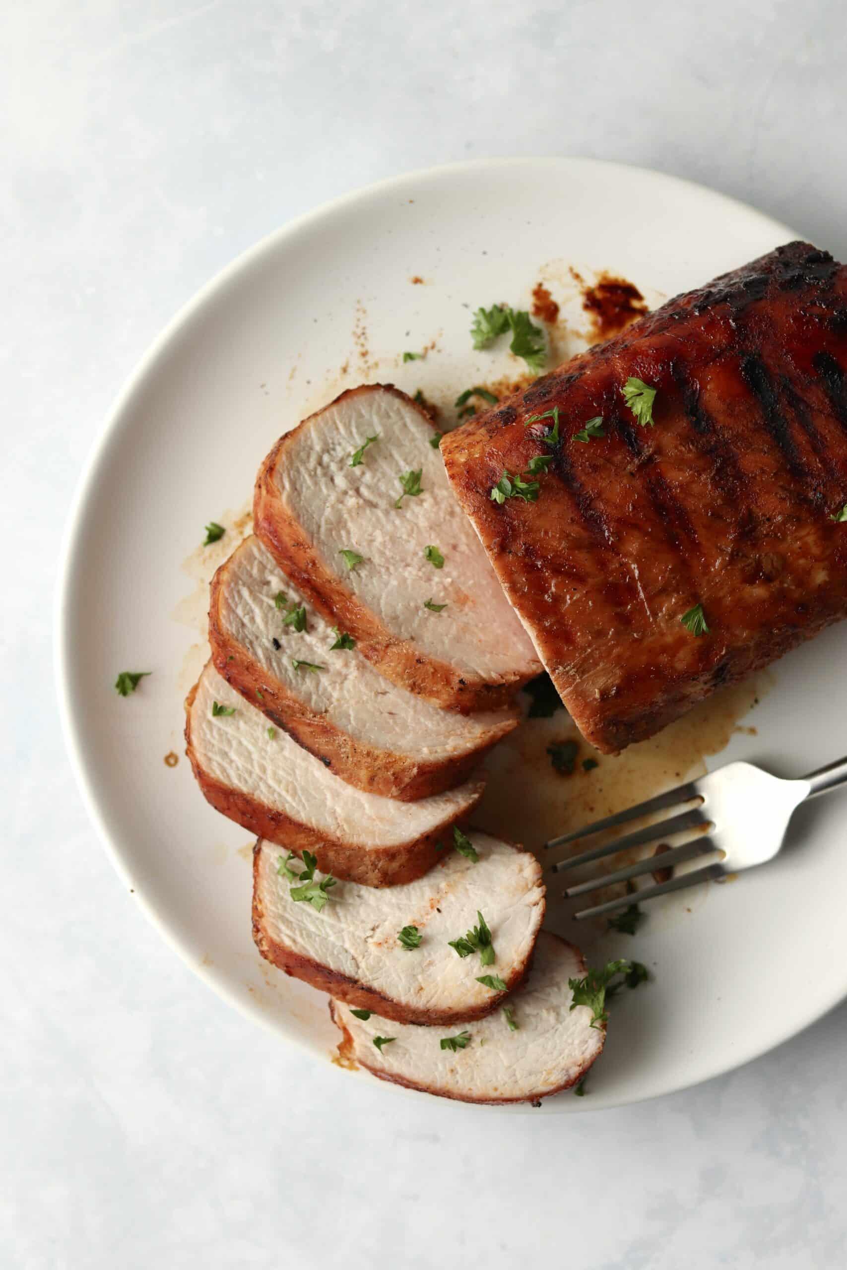 sliced pork tenderloin on the grill