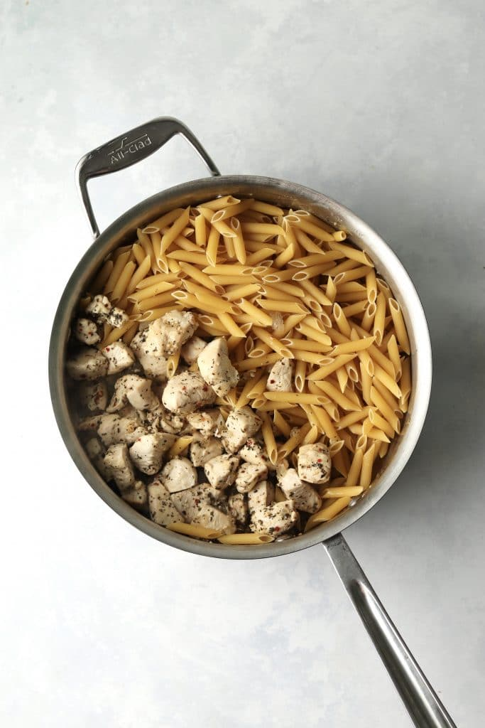 Uncooked pasta and cooked chicken in a pan