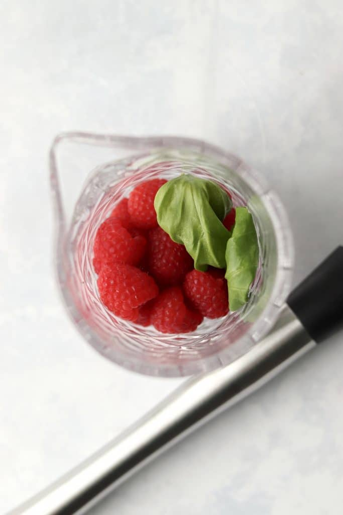 Raspberries and basil in a cocktail pitcher