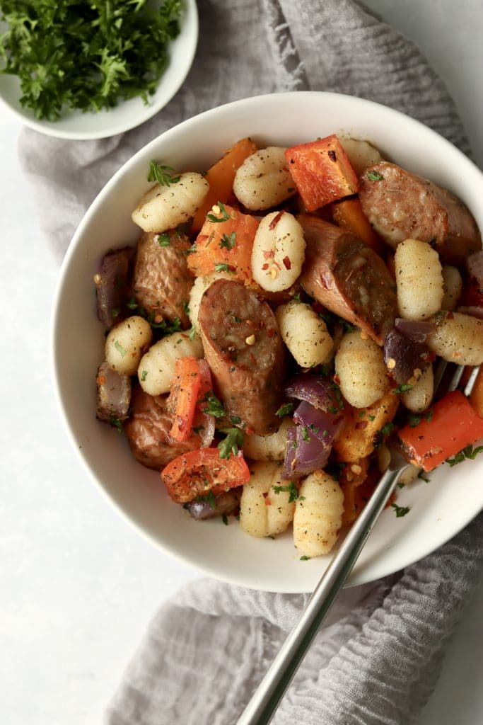 roasted gnocchi, sausage, and veggies in a bowl with fresh herbs