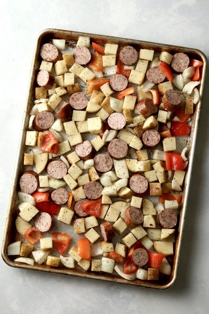 potatoes, peppers, onions, and sliced sausage on sheet pan